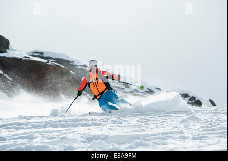 Man skiing downhill powder snow Alps - Stock Photo