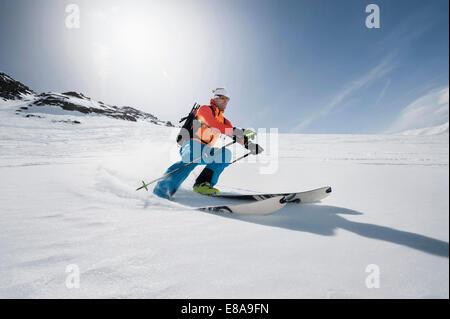 Man skiing downhill powder snow Alps sunshine - Stock Photo