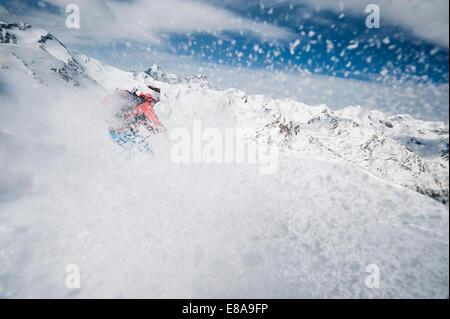 Skier woman downhill powder snow Alps - Stock Photo