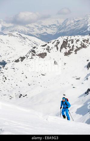Man climbing mountain Alps snow winter - Stock Photo