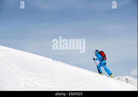 Man climbing ski slope mountain Alps snow winter - Stock Photo