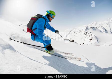 Man skier skiing downhill steep slope Alps - Stock Photo
