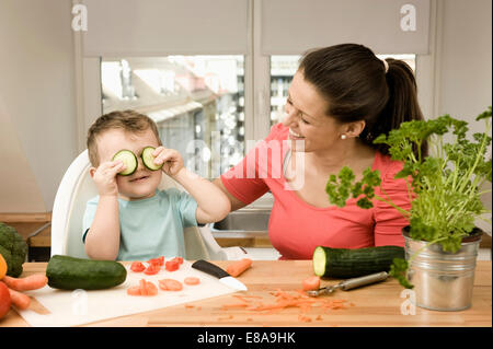 Mother and son preparing vegetables in kitchen, smiling - Stock Photo