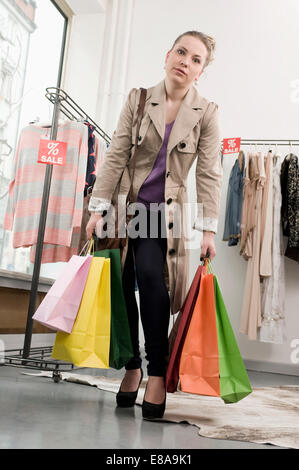 Portrait of young woman holding shopping bags - Stock Photo