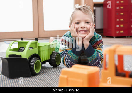 Portrait of smiling little boy with head in his hands lying on ground of his kindergarten - Stock Photo