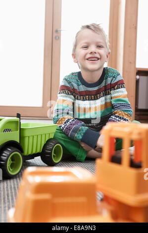 Portrait of smiling little boy sitting on ground of his kindergarten - Stock Photo