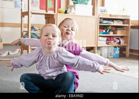 Portrait of two little sisters in kindergarten sticking out tongues - Stock Photo