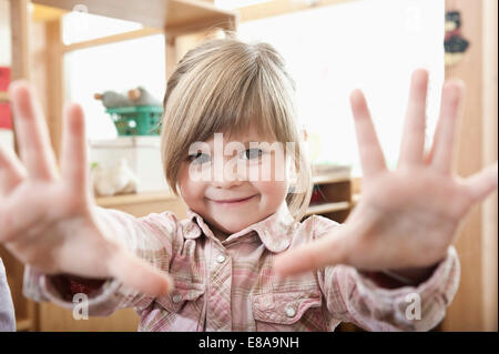 Portrait of smiling little girl showing her hands - Stock Photo