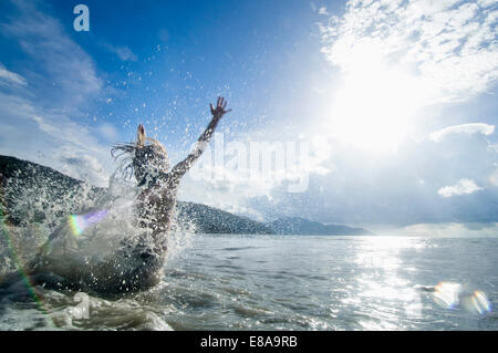 woman jumping into the ocean, Penang, Malaysia - Stock Photo