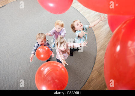 Four kids playing with red balloons in kindergarten, elevated view - Stock Photo