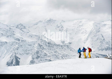 Alps winter mountains three skiers snow - Stock Photo