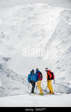 Three skiers winter snow standing mountains - Stock Photo