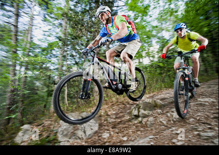 Two Mountainbikers stunt racing forest track - Stock Photo