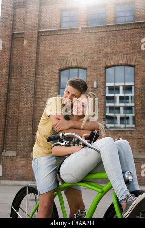 Portrait of teenage couple embracing on bicycle, smiling - Stock Photo