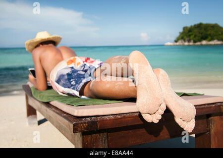 teenage boy hearing music at beach, Koh Lipe, Thailand - Stock Photo