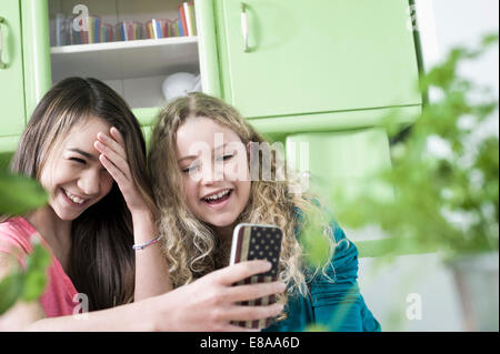 Girls in kitchen with smart phone - Stock Photo