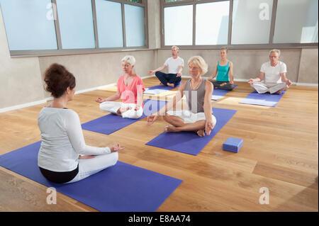 Yoga class instructor senior group meditation - Stock Photo