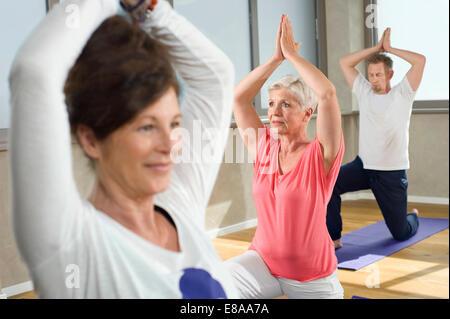 Close up Yoga class female instructor senior group - Stock Photo