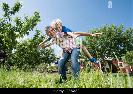 Son boy father piggyback garden playing fun - Stock Photo