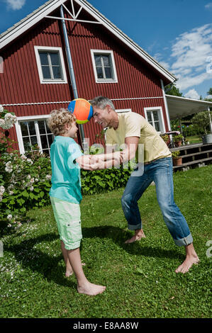 Father son balancing football playing fun garden - Stock Photo