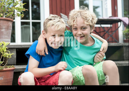 Friends young boys sitting steps house smiling - Stock Photo