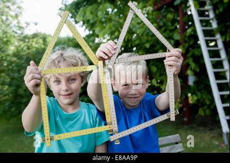 Close up two boys house shape ruler - Stock Photo