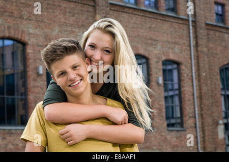 Portrait of teenage couple embracing each other, smiling - Stock Photo
