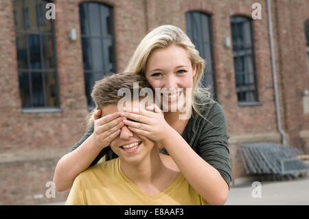 Portrait of teenage girl covering eyes of teenage boy, smiling - Stock Photo