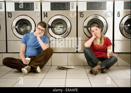 Portrait of young couple sitting on floor - Stock Photo