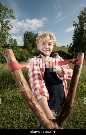 Young boy blond holding wooden slingshot - Stock Photo