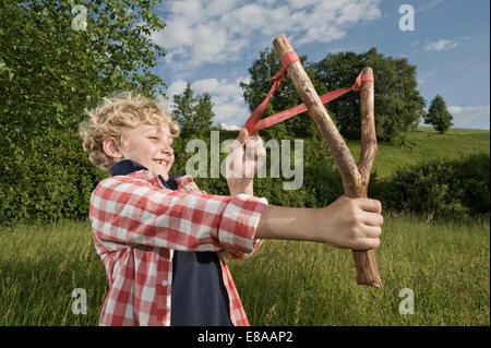 Boy holding handmade wooden slingshot - Stock Photo