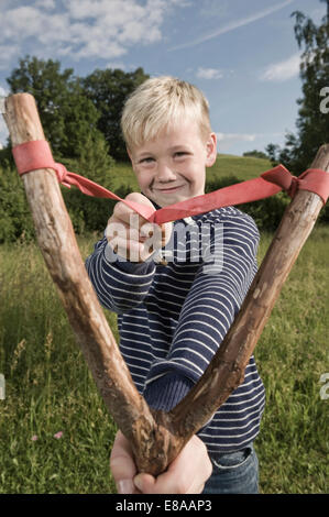 Young boy holding wooden slingshot smiling - Stock Photo