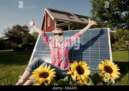 Sunbathing solar panel woman garden happy - Stock Photo