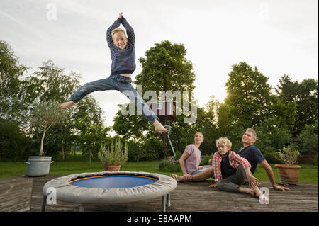 Young family garden boy jumping trampoline - Stock Photo