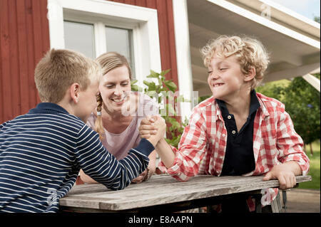 Two young boys arm wrestling mother watching - Stock Photo
