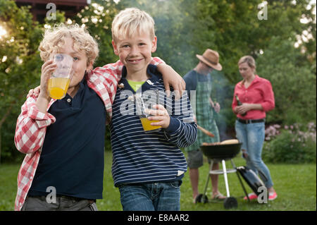 Family barbecue parents boys friends garden - Stock Photo