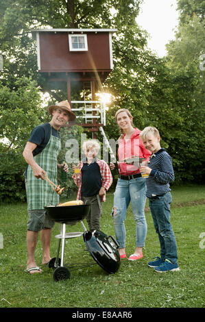 Young family garden barbecue kids tree-house - Stock Photo