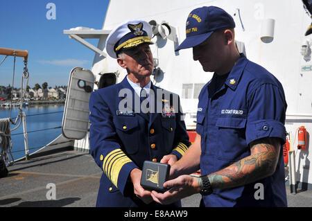 Commandant of the U.S. Coast Guard Adm. Paul Zukunft, left, recognizes Petty Officer 2nd Class Matthew Baasch, right, - Stock Photo