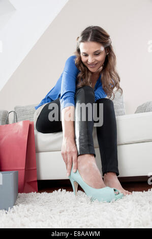 Portrait of young woman sitting on couch at home trying on new high heels - Stock Photo