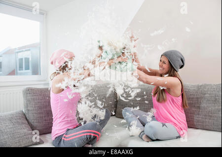 Two female friends sitting on couch at home having pillow fight - Stock Photo