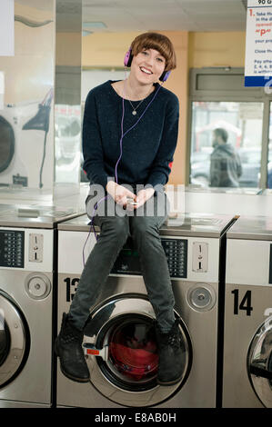 Young woman listening music on top of washing machine, smiling - Stock Photo
