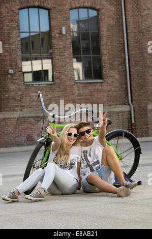 Teenage couple sitting on street with bicycle and showing peace sign, smiling - Stock Photo