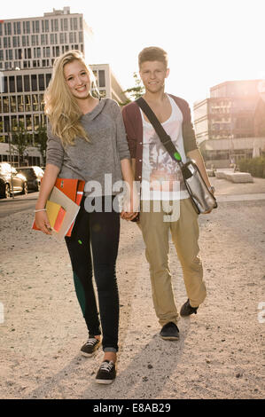 Portrait of teenage couple coming from school, smiling - Stock Photo