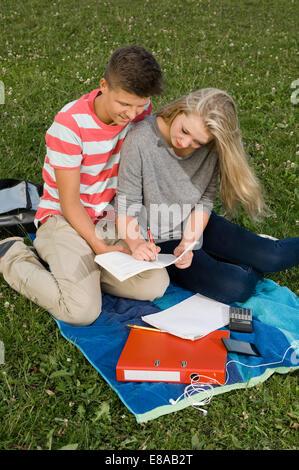 Teenage couple doing homework in park - Stock Photo