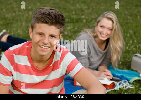 Portrait of teenage couple in park, smiling - Stock Photo