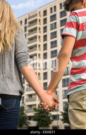 Teenage couple holding hands, close up - Stock Photo