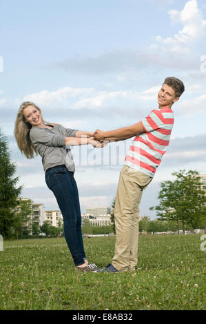 Portrait of teenage couple holding hands in park, smiling - Stock Photo