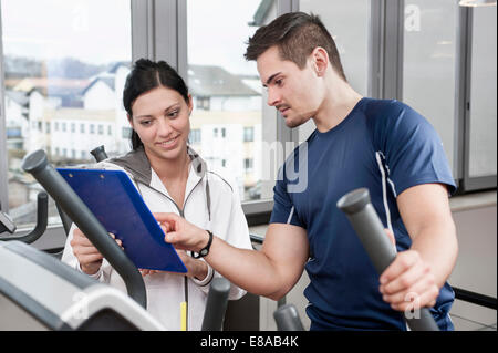 Young woman and man in gym - Stock Photo