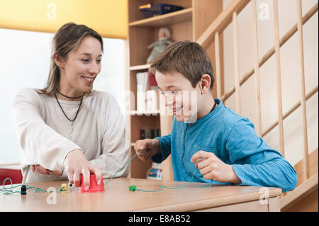 Portrait of playing boy and female childcare assistant - Stock Photo