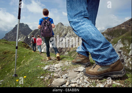 Father teenage kids hiking in mountains Alps - Stock Photo